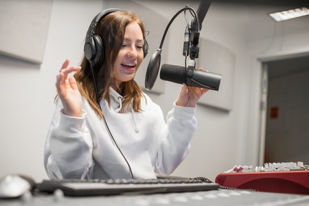 Female Host Communicating On Microphone In Radio Studio Stock Photo