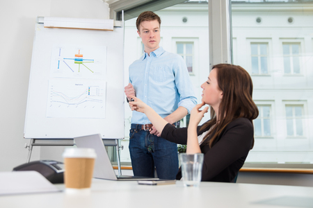 Businessman Looking At Female Coworker Pointing On Chart