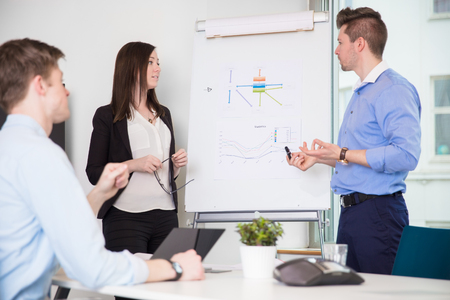 Executive Explaining Chart To Coworkers In Office Stock Photo