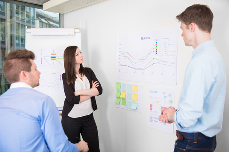 Business People Discussing Over Line Graph In Office Stock Photo