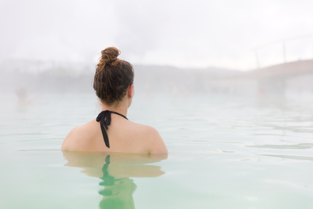 Woman Relaxing In geothermal hot spring At Iceland