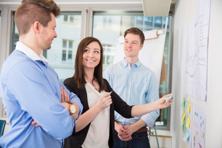 Businesswoman Sticking Adhesive Notes While Standing With Collea Stock Photo