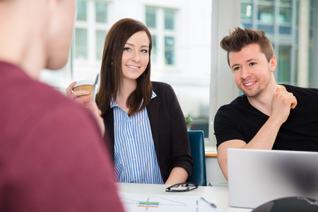 Business People Smiling While Looking At Colleague At Desk Stock Photo