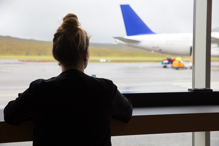 Woman Looking At Airplane Through Window At Airport Stock Photo