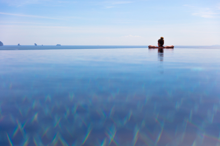 Woman Resting In Infinity Pool At a Aonang Beach Resort Stock Photo