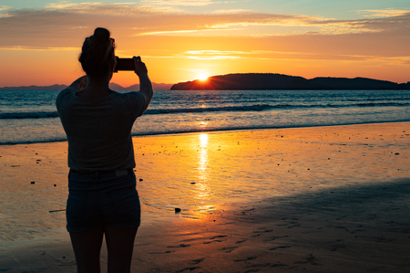 Silhouette Female Tourist Photographing Sea At Beach During Suns