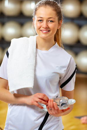 Smiling woman holding water bottle at fitness gym