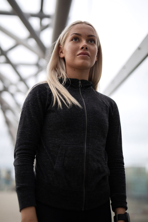 Urban scandinavian woman in workout outfit standing on a bridge