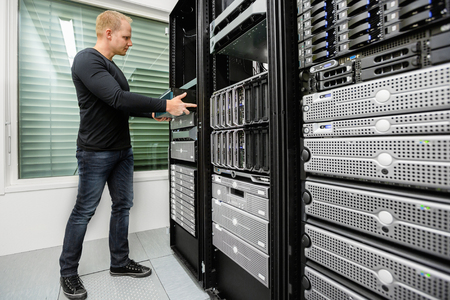 Male Technical Consultant Installing Router In SAN At Datacenter