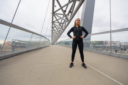 Confident Woman with Hands on the Hips in Workout Outfit Standing on Bridge 版權商用圖片