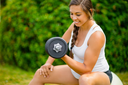 Expectant Female Exercising With Dumbbells To Strengthen Arms In Banco de Imagens