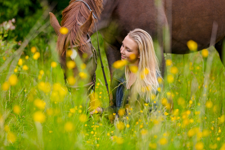 Smiling woman sits in the meadow with her beautiful arabian horse Imagens