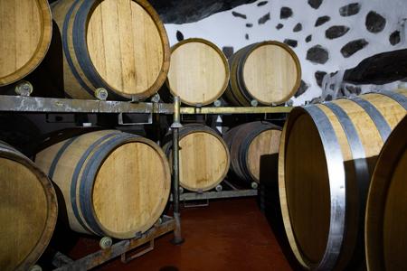 Wooden Barrels in Oak Stored At Wine Cellar Below Ground Stock Photo