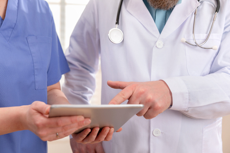 Arzt und Krankenschwester diskutieren Patiententests am Tablet-Computer im Krankenhaus