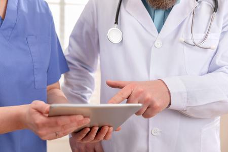 Médico y enfermera discutiendo las pruebas de los pacientes en la tableta en el hospital