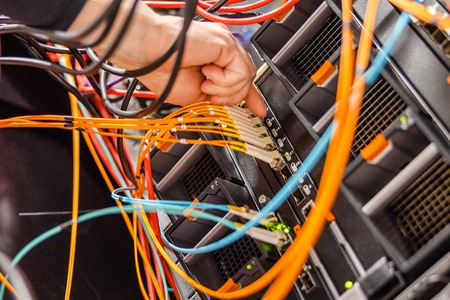 Male IT Engineer Plugging High Speed Fiber Cable In Network Switch Reklamní fotografie