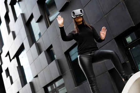 Dedicated Woman Wearing Virtual Reality Technology Glasses Against Building Imagens