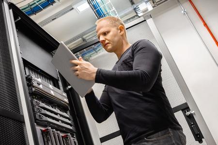 Técnico masculino con tableta digital en el centro de datos para monitorear SAN y servidores
