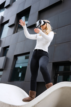 Woman Wearing Virtual Reality Glasses In Front Of Futuristic City Building Wall Imagens - 124959018