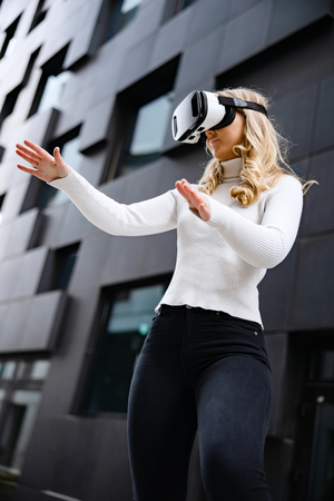 Woman Wearing Virtual Reality Glasses Against Contemporary City Building