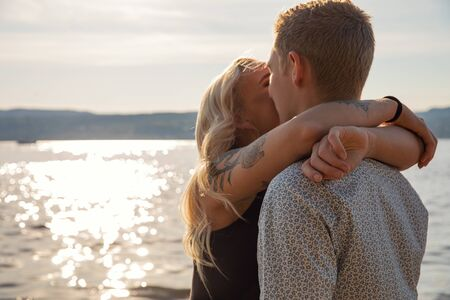 Kissing couple in romantic embrace on beach at summer Reklamní fotografie