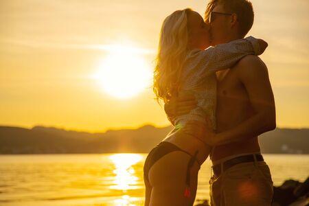 Young Man Kissing Girlfriend Standing At Beach In Beautiful Sunset Reklamní fotografie