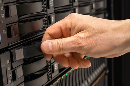 Male IT Professional Replacing Server Drive in SAN Rack