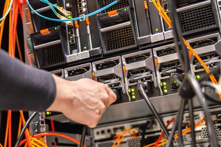 Male Technician Plugging Power Cable to Blade Server Cluster in Datacenter