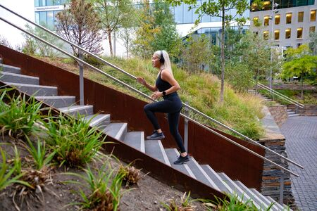 Fitness women running fast intervals in stairs in city park