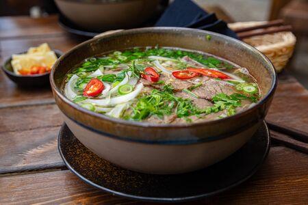 Nahaufnahme von frischer Pho-Suppe in Schüssel auf dem Tisch serviert