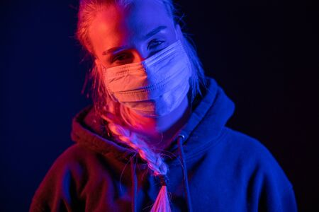 Exhausted or sick woman in protective face mask with multi colored lights Foto de archivo - 145346486