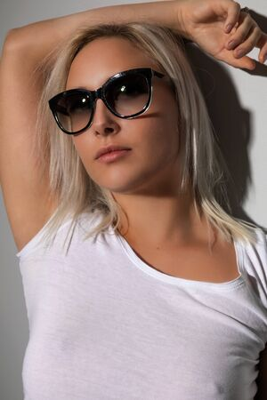 Attractive blonde woman with sunglasses in sun light with shadows