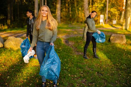 Young female volunteer in a team holding garbage bag at park