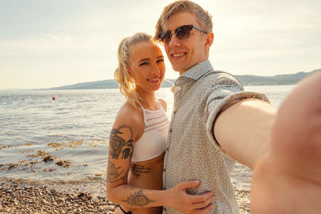 Smiling Young Man Taking Selfie With Girlfriend At Beach
