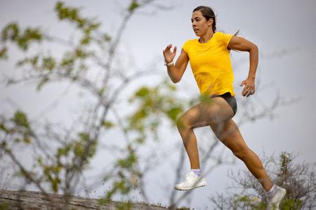 Confident Woman Sprinting On Mountain Against Sky Reklamní fotografie