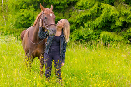 Smiling young woman feeding her arabian horse with snacks in the field Imagens