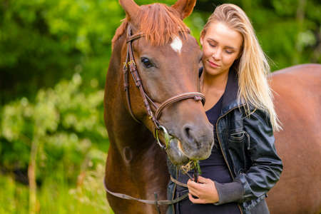 Beautiful young woman with her arabian horse in the field