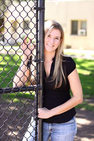 Blond woman standing by a gate