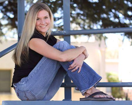 bleachers: Blond woman sitting in bleachers at a park Stock Photo