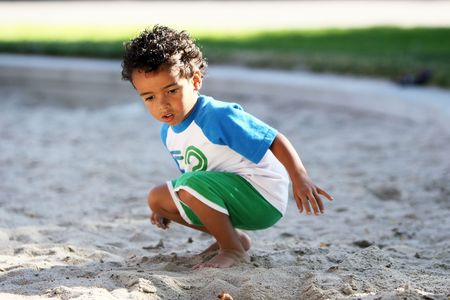 squatting down: A little boy, squatting down over the sand, looking through it for rocks. Stock Photo