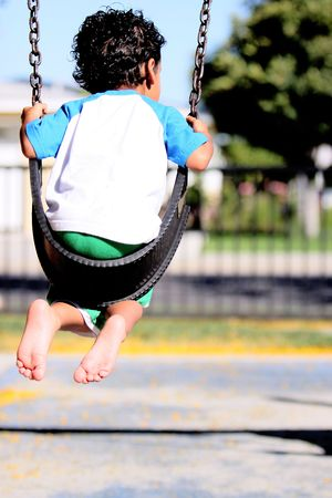 A boy, on a swing, with his back to the camera, and the bottom of his bare feet showing.