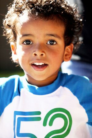 A cute little boy with dark curly hair, and big brown eyes. photo