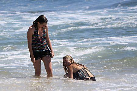 2 若い女性は、浜の水で遊ぶ。1 つは両方ともちょうど大きな波でヒット得たのでにこにこしています。 写真素材 - 7506867