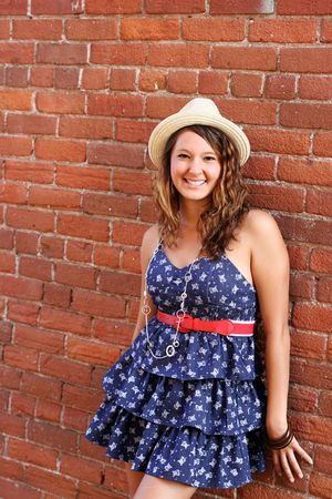 A pretty young girl wearing a blue dress and a hat, leaning against a brick wall.
