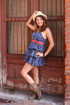 フリルのドレスと帽子、路地でドアがかわいい女の子。 写真素材 - 7506869