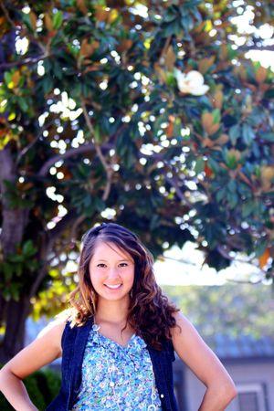 マグノリアの木の前の地面に立っている美少女。 写真素材 - 7506863