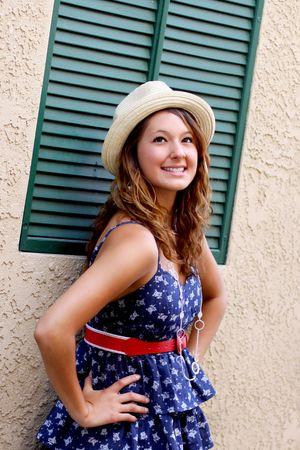 かわいい女の子はドレスと帽子見て、笑って、建物に緑のシャッター近くに立っています。 写真素材 - 7506873