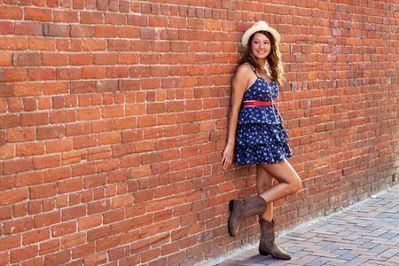 幸せなかわいい女の子レンガの路地に立って、彼女の顔に笑みを浮かべて、側を見つめてします。 写真素材 - 7507436