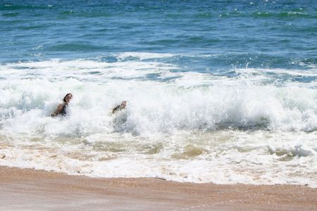 overtaken: Two young women, being overtaken by a wave at the beach.