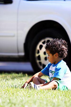 Een kleine jongen zittend op het gras steen bolk.